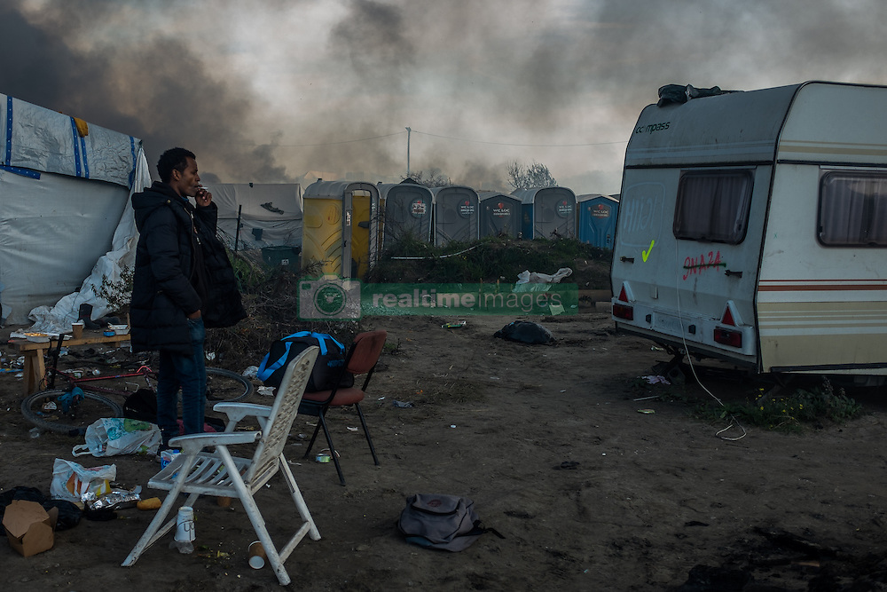 October 26, 2016 - Calais, France - A Migrant smokes a cigarette in the Calais Jungle, on October 26, 2016. Huge fires destroyed a mayor part of the refugee camp today. (Credit Image: © Markus Heine/NurPhoto via ZUMA Press)