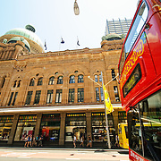 The Queen Victoria Building (QVB) on George Street with a doubledecker red sightseeing bus at right