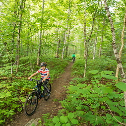 A boy and his mom ride mountain bikes on a trail near Deboullie Pond in Aroostook County, Maine. Deboullie Public Reserve Land.