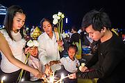 02 FEBRUARY 2013 - PHNOM PENH, CAMBODIA:  Cambodians light candles and incense before praying for former King Norodom Sihanouk in Phnom Penh. Much of Phnom Penh has been shut down to honor former King Norodom Sihanouk, who ruled Cambodia from independence in 1953 until he was overthrown by a military coup in 1970. Only bars, restaurants and hotels that cater to foreign tourists are supposed to be open. The only music being played publicly is classical Khmer music. Sihanouk died in Beijing, China, in October 2012 and will be cremated during a state funeral royal ceremony on Monday, Feb. 4.    PHOTO BY JACK KURTZ