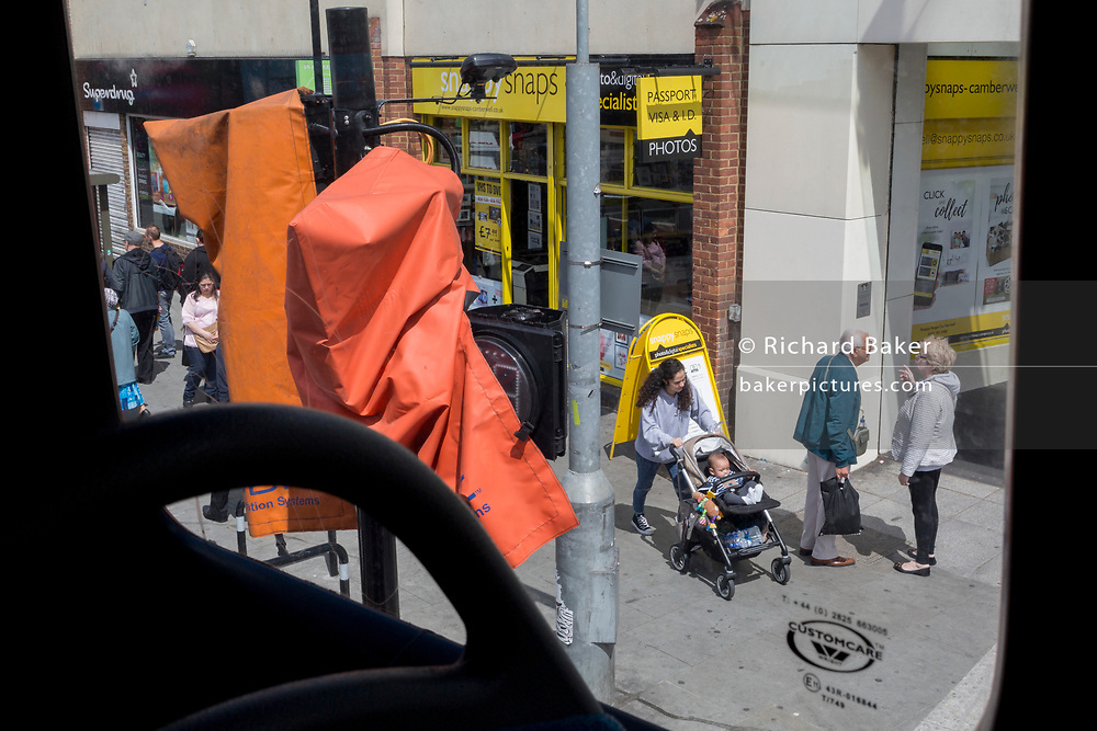 Covered traffic lights and an elderly couple on Butterfly Walk in Camberwell, on 17th June 2019, in south London, England.