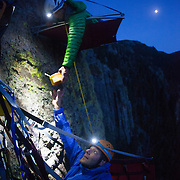 Jonathan Thompson lies on a portoledge where he camped for the night in Estes Park, here receiving his dinner from climbing instructor Brett Bloxom. 200 meters up a cliff.