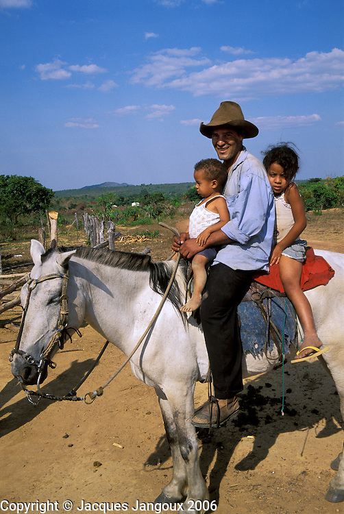Father on horseback with two children, Brazilian Highlands, Goias, Brazil