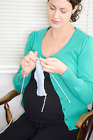 Pregnant woman knitting in chair