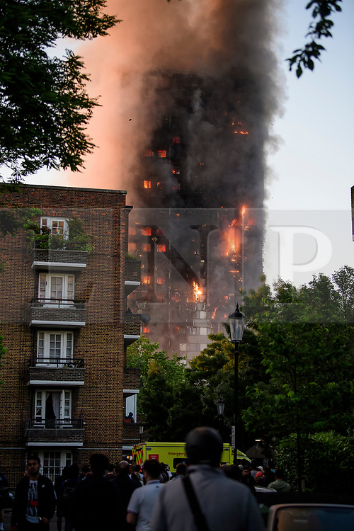 © Licensed to London News Pictures. 14/06/2017. London, UK. Fire fighters tackle a blaze at the scene of a huge fire at Grenfell tower block in White City, London. The blaze engulfed the 27-storey building with 200 firefighters attending the scene. There were reports of people trapped in the building. Photo credit: Ben Cawthra/LNP