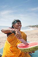 Happy mature Indian woman cutting watermelon at Vagator Beach