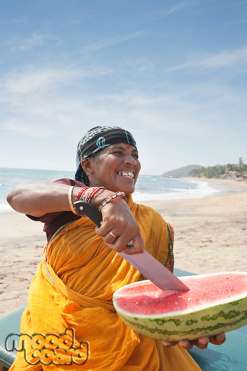 Happy mature Indian woman cutting watermelon at Vagator Beach