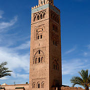 The Koutoubia Mosque or Kutubiyya Mosque is the largest mosque in Marrakesh, Morocco. The mosque is also known by several other names, such as Jami' al-Kutubiyah, Kotoubia Mosque, Kutubiya Mosque, Kutubiyyin Mosque, and Mosque of the Booksellers. It is located in the southwest medina quarter of Marrakesh. The mosque is ornamented with curved windows, a band of ceramic inlay, pointed merlons, and decorative arches; it has a large plaza with gardens, and is floodlit at night. The minaret, 77 metres (253 ft) in height, includes a spire and orbs. It was completed under the reign of the Almohad Caliph Yaqub al-Mansur (1184 to 1199), and has inspired other buildings such as the Giralda of Seville and the Hassan Tower of Rabat.