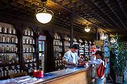 Customer shopping in Farmacia Dr A Alonso Nunez shop with old medicine bottles display in Calle Ancha, Leon, Castilla y Leon, Spain