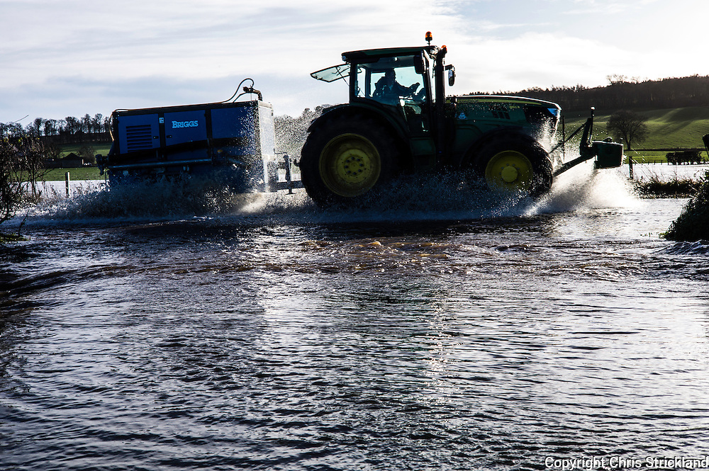 Crailing, Jedburgh, Scottish Borders, UK. 6th December 2015. A tractor pulling a water pump system drives through flood water on the A698 between Jedburgh and Kelso in the Scottish Borders.