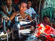 09 NOVEMBER 2014 - SITTWE, RAKHINE, MYANMAR: A Rohingya Muslim does tailoring in his shop in a market in a Rohingya Muslim IDP camp near Sittwe. After sectarian violence devastated Rohingya communities and left hundreds of Rohingya dead in 2012, the government of Myanmar forced more than 140,000 Rohingya Muslims who used to live in and around Sittwe, Myanmar, into squalid Internal Displaced Persons camps. The government says the Rohingya are not Burmese citizens, that they are illegal immigrants from Bangladesh. The Bangladesh government says the Rohingya are Burmese and the Rohingya insist that they have lived in Burma for generations. The camps are about 20 minutes from Sittwe but the Rohingya who live in the camps are not allowed to leave without government permission. They are not allowed to work outside the camps, they are not allowed to go to Sittwe to use the hospital, go to school or do business. The camps have no electricity. Water is delivered through community wells. There are small schools funded by NOGs in the camps and a few private clinics but medical care is costly and not reliable.  PHOTO BY JACK KURTZ