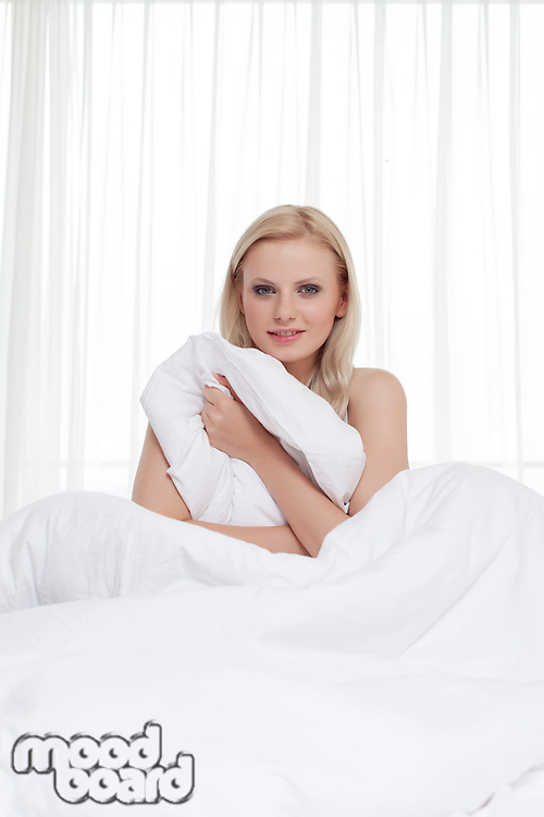 Portrait of beautiful young woman holding bedsheet in bed