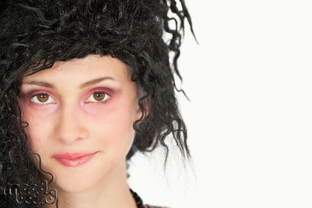 Close-up portrait of beautiful young woman with teased hair over gray background