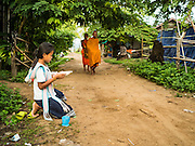 """20 JUNE 2016 - DON KHONE, CHAMPASAK, LAOS:  Girls wait to present alms to monks from Wat Khone Nua on their morning alms' rounds, called the """"tak bat"""" in Don Khone village on Don Khone Island. Don Khone Island, one of the larger islands in the 4,000 Islands chain on the Mekong River in southern Laos. The island has become a backpacker hot spot, there are lots of guest houses and small restaurants on the north end of the island.    PHOTO BY JACK KURTZ"""