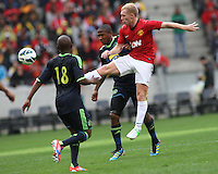 Manchester United's Paul Scholes against Ajax Cape Town's Thembinkosi Fanteni and Paul Rusike during their International friendly match at Cape Town Stadium