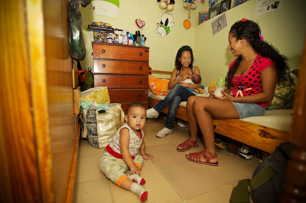 15-year-old mother, Yanaifre Acevedo, (center) breast-feeds her newborn baby, Dilan, in a slum in Caracas, Venezuela with her sister, Keisy Acevedo who also got pregnant at 15-years old with her son John, seated on the floor.  Acevedo, who wants to be a professional dancer, said she got pregnant by accident, but that she has a secret plan to have her aunt watch her baby so that she can go back to school. She also plans to get a job so that she and her boyfriend can move into their own apartment together. She says her boyfriend is excited to be a father, but he has hardly visited her and their son.