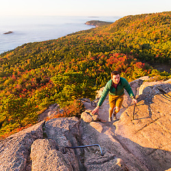 "A man hiking ""The Beehive"" in fall in Maine's Acadia National Park."