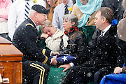 Major General Robert Williams, left, hands the American flag to Teena and Michael Nemelka, parents of fallen U.S. Army Pfc. Aaron Nemelka, during a burial ceremony at Camp Williams, Saturday,  Nov. 14, 2009 in Riverton, Utah. Nemelka was one of 13 gunned down at Fort Hood, Texas. Also pictured is Lindsay Nemelka, second from left, sister-in-law to Nemelka. (AP Photo/Colin Braley)