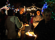 Dennis Wardle, center left, warms his hands over an open fire during the annual Christkindlmarket lantern parade and Christmas tree lighting ceremony at This Is The Place Heritage Park, Thursday, Nov. 29, 2012.