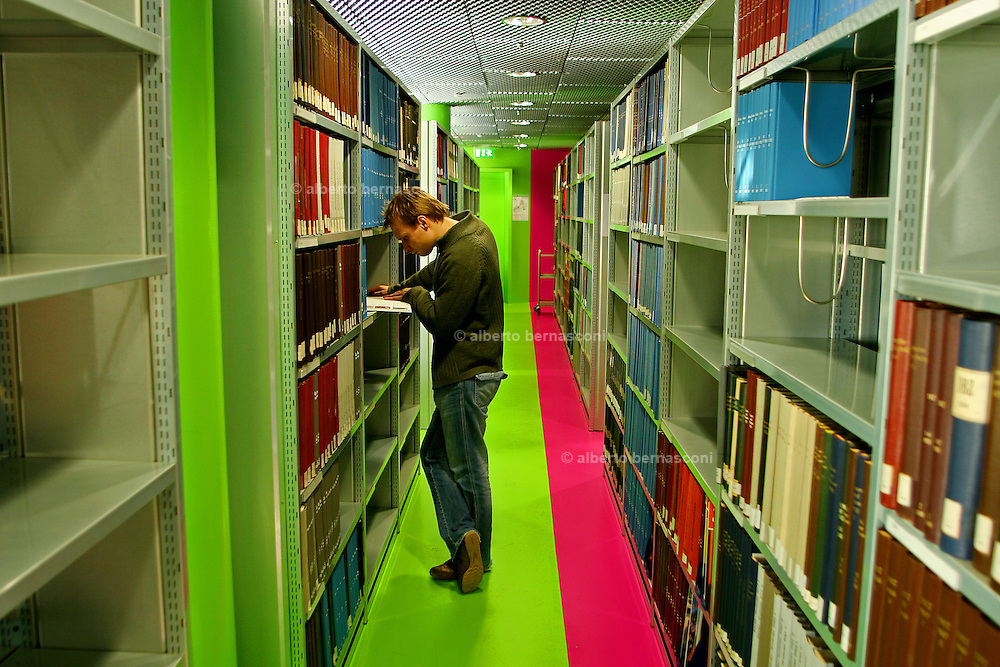 Germany, Cottbus, the library designed by architect Herzog et de Meuron. ..An organic, amoeba-like form, it is not immediately obvious which is the front and which is the rear of the building. Inside, too, the seven upper and two basement levels of the library are all different in design: only their external form stays the same. But it is not only the design of the academic library - with its brightly coloured spiral staircase coiling upwards - which is unique; so too is its organisational form. The Information, Communication and Media Center (ICMC) at Brandenburg Technical University in Cottbus creates close proximity between areas which other universities have traditionally kept apart - in both physical and institutional terms. Behind the milky glass façade, imprinted with letters from many alphabets, the library, multimedia centre, computer centre and data processing unit all work hand in hand. (text from the Goethe Institut website)