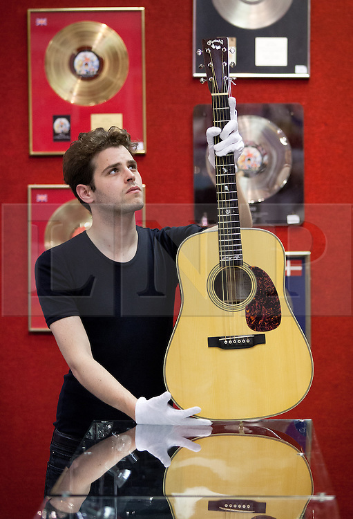 © Licensed to London News Pictures. 28/06/2013. London, UK. A Bonhams employee holds a 'Martin Special 2007' acoustic guitar (est. GB£10,000-15,000) owned and played by Led Zeppelin guitarist Jimmy Page in London today (28/06/2013) at the press view for an entertainments auction being held at Bonham's Knightsbridge premises on the 3rd of July 2013. Photo credit: Matt Cetti-Roberts/LNP