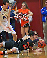 Post Falls High's Marcus Colbert looks for a teammate to pass to after diving for a loose ball in front of Ty Higbie from Coeur d'Alene High in the second half.