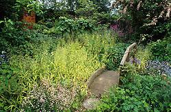 Bridge in a wild, woodland area in a small town garden with Milium effusum 'Aureum'