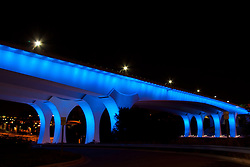 New I-35W Bridge over the Mississippi River in Minneapolis Minnesota lit up at night with radiant blue lights.