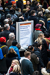 © Licensed to London News Pictures. 26/02/2018. London, UK. A sign warns commuters of train delays and cancellations because of cold weather as they wait at Liverpool Street Station. Severe cold, blizzards and heavy snow are expected as the 'Beast from the East' brings freezing Siberian air to the UK. Photo credit: Rob Pinney/LNP