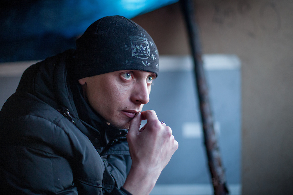 "Portrait of activist Andrej at the barricades blockading a building supplies store named ""Epicenter"" in the city of Lviv, Ukraine. In the back visitors and activists."