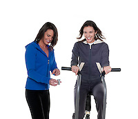 Young caucasian woman trainning in the gym with personal trainer woman.