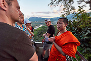 Laos. Luang Prabang. Mount Phousi. Sunset view over Luang Prabang and surroundings from Wat Chom Si. Buddhist monk chatting with tourists.