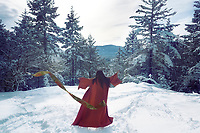 Artistic photo of the back of an asian woman in red kimono dancing, spinning around on the snow in winter forest tossing her obi belt away