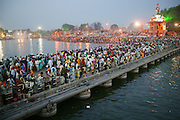 A crowd gathers before dawn on a bridge over the Shipra River which flows through the holy city of Ujjain, in the central Indian state of Madhya Pradesh during the Hindu festival of Kumbh Mela. Every 12 years, millions of devout Hindus celebrate the month-long festival of Kumbh Mela by bathing in the Shipras holy waters. Hundreds of ashrams set up dusty, sprawling camps that stretch for miles. Under the watchful eye of police and lifeguards, the Patkar family of Ujjain, India join the faithful throng in the cool of the evening and bathe in the river, too. Hungry Planet: What the World Eats (p. 169).
