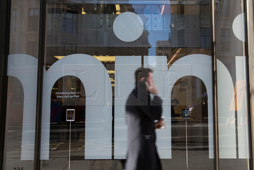 © licensed to London News Pictures. London, UK 02/11/2012. People walking past Apple Store which features iPad Mini on its window on Regent Street, London as highly anticipated tablet meets the costumers on 02/11/12. Photo credit: Tolga Akmen/LNP