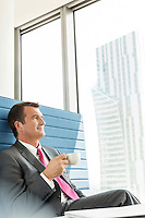 Mature businessman having coffee in office
