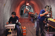 Physics: Aligning Magnets in the 3 km tunnel of the Stanford Linear Accelerator Center (SLAC), Menlo Park, California.  Reverse Bend SLC Experiment, [1986].Technicians making final alignment checks in the tunnel of the Stanford Linear Collider (SLC). The SLC was built from the 3km linear accelerator at Stanford, California. In the SLC, electrons and positrons are accelerated to energies of 50 giga electron volts (GeV) before being forced to collide. In this collision, a Z-nought particle may be produced. The Z-nought is the mediator of the electroweak nuclear force, the force behind radioactive decay. The first Z-nought was detected at SLC on 11 April 1989, six years after its discovery at the European LEP accelerator ring, near Geneva..