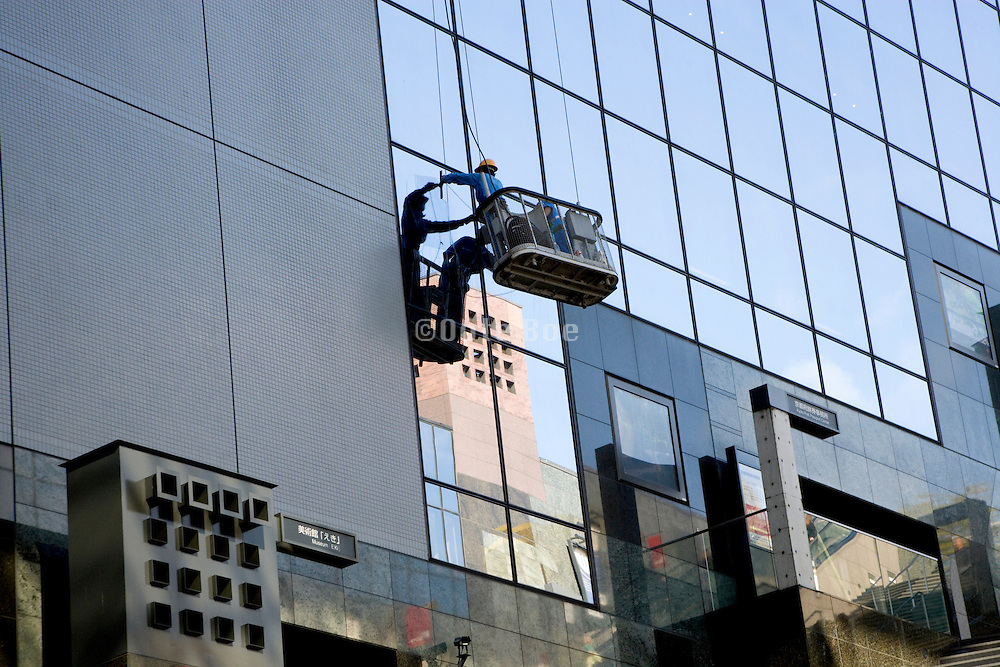 window cleaner hanging dangerous far out of his basket while cleaning windows high up