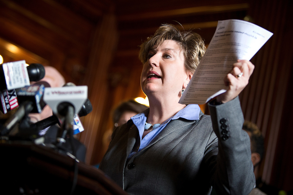 MADISON, WI — FEBRUARY 25: State Senator Jennifer Shilling holds up a Milwaukee Journal Sentinel newspaper clipping during a press conference in the Wisconsin Capitol on Wednesday morning before a legislative session.