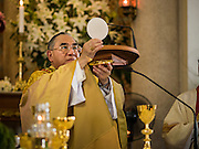 18 SEPTEMBER 2016 - BANGKOK, THAILAND:  FRANCIS XAVIER KRIENGSAK, the Archbishop of Bangkok, consecrates the communion host during the 100th anniversary mass at Santa Cruz Church. Santa Cruz Church was establised in 1769 to serve Portuguese soldiers in the employ of King Taksin, who reestablished the Siamese (Thai) empire after the Burmese sacked the ancient Siamese capital of Ayutthaya. The church was one of the first Catholic churches in Bangkok and is one of the most historic Catholic churches in Thailand. The first sanctuary was a simple wood and thatch structure and burned down in the 1800s. The church is in its third sanctuary and was designed in a Renaissance / Neo-Classical style. It was consecrated in September, 1916. The church, located on the Chao Phraya River, serves as a landmark for central Bangkok.      PHOTO BY JACK KURTZ