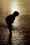 Silhouette of a young girl looking for fish and shells in the shallow water of the ocean.