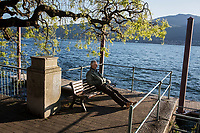 VERBANIA, ITALY - 18 APRIL 2017: A man relaxes by the Lake Maggiore in Verbania, Italy, on April 18th 2017.<br /> <br /> Emma Morano was an Italian supercentenarian who, prior to her death at the age of 117 years and 137 days, was the world's oldest living person whose age had been verified, and the last living person to have been verified as being born in the 1800s. She died on April 15th 2017.