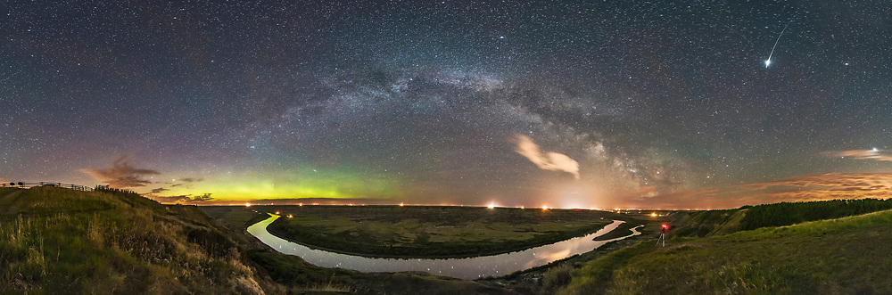 The Milky Way arching over the scenic bend of the Red Deer River, Alberta, from the Orkney Viewpoint overlooking the Badlands and river valley, in a 300&deg; panorama. To the north at left, a weak aurora shines along the horizon. Bands of airglow also colour the sky to the east at centre.<br /> <br /> To the south at right of centre, the Milky Way becomes lost amid the light pollution from Drumheller, Alberta, made more obvious by some clouds drifting through. <br /> <br /> One of my cameras is at right, shooting a time-lapse sequence. <br /> <br /> A bright Iridium satellite flare is at right, caught one of the panorama frames. Jupiter is at far right. <br /> <br /> And of course, I like the way the curve of the Milky Way is mirrored in the curve of the river, which is why I picked this spot and this night in spring, when the Milky Way is still arching across the east and not overhead as it is later in summer. <br /> <br /> This is a stitch of 6 segments with the Rokinon 12mm lens, in landscape mode, and Nikon D750. Each 45 seconds at f/2.8 and ISO 3200. Stitched with PTGui. Taken on a mild and moonless night, May 20, 2017.