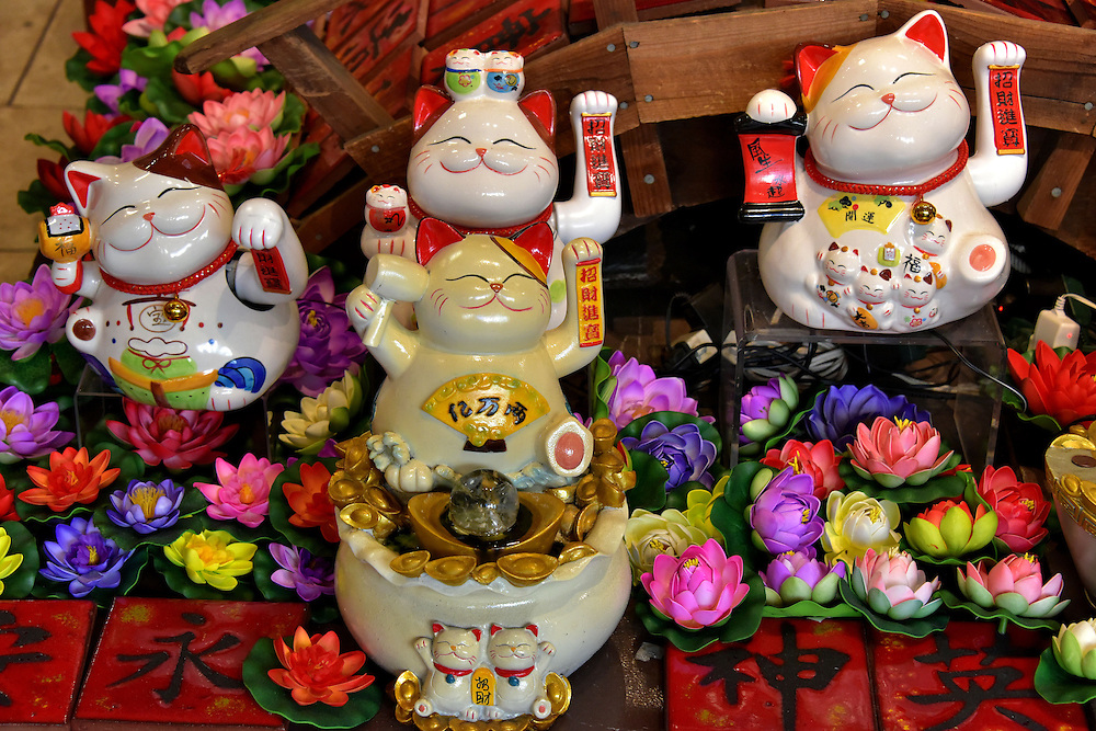 Maneki-neko Beckoning Cat Display in San Francisco, California<br /> These waving porcelain cats are called Maneki-neko in Japanese.  I assumed they were another souvenir for tourists visiting Chinatown.  But by tradition, they supposedly give good luck to the owner.  And when they are placed in front of a store with a moving left paw, which the four were doing in this display, they are beckoning customers to come inside.