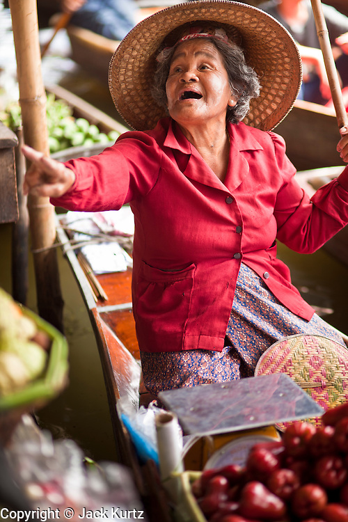 """10 JULY 2011 - DAMNOEN SADUAK, RATCHABURI, THAILAND:  A vendor in the floating market in Damnoen Saduak, Thailand, looks for customers while she sells fresh fruit from her boat. The Thai countryside south of Bangkok is crisscrossed with canals, some large enough to accommodate small commercial boats and small barges, some barely large enough for a small canoe. People who live near the canals use them for everything from domestic water to transportation and fishing. Some, like the canals in Amphawa and nearby Damnoensaduak (also spelled Damnoen Saduak) in Rajburi  province (also spelled Ratchaburi) are also relatively famous for their """"floating markets"""" where vendors set up their canoes and boats as floating shops.     PHOTO BY JACK KURTZ"""