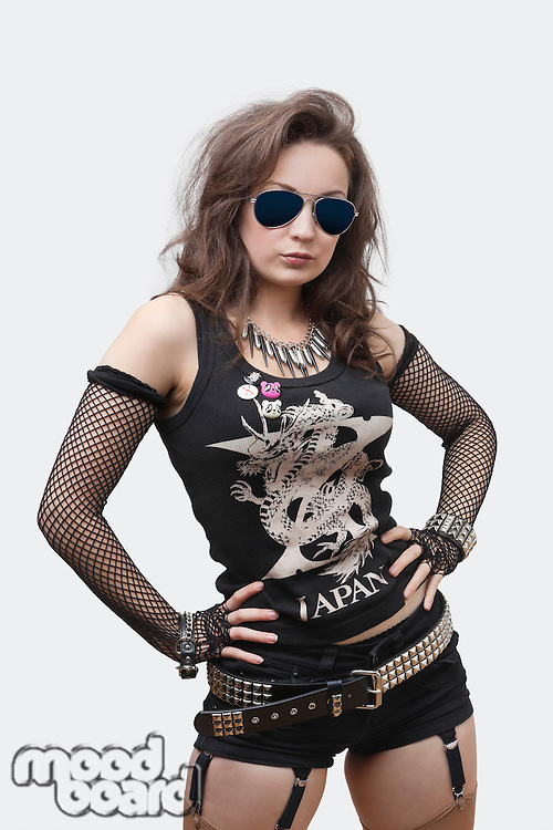 Portrait of gothic young woman with hands on hips over white background