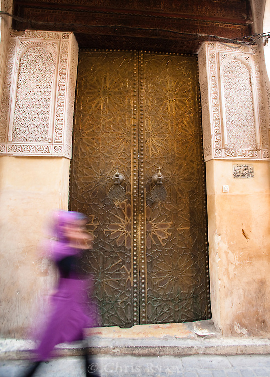 Woman in colorful dress walking by madersa gate, Fez medina, Morocco