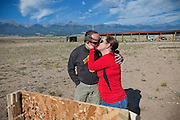 John Daniel Shannon, 48, a former US Army Senior Sniper, is kissing his wife, Torrey Shannon, 42, in a shooting range near his home in Westcliffe, CO, USA, where he retired with his family after a serious brain injury inflicted by an insurgent sniper in Ramadi, Al Anbar Province, Iraq, on November 13th 2004. Daniel fought during the Second Battle of Fallujah and was then moved to nearby Ramadi. Daniel lost his left eye and has multiple health issues because of his injury: memory problems, balance problems, he can't smell and taste well anymore, he suffers from PTSD, has  troubles with large crowds and city surroundings. This is the reason why he and his family moved to a quiet location on the Rocky Mountains. In 2007 Dan helped the Washington Post to uncover patients' neglect at the Walter Reed Army Medical Center; he also testified before Congress. Torrey, his wife, is a freelance writer and a contributor for the Huffington Post; she's also campaigning to improve the situation of veterans' families.