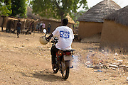 A health worker rides a motorcycle in the village of Gbulahabila, northern Ghana on Wednesday March 25, 2009.
