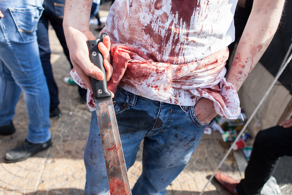 Young shiite muslim man, covered in his own blood, carrying a bloody knife, commemorating the Day of Ashura, in Nabatieh, Lebanon (November 14, 2013).